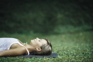Girl doing yoga, meditating, Shavasana or corpse position